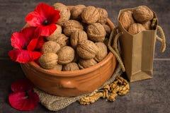 Грецкие орехи в керамическом шаре и красных маках Стоковые Фотографии RF