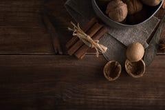 Грецкие орехи в шаре металла, темная предпосылка Раковина и циннамон грецкого ореха на деревянном столе Стоковые Изображения RF
