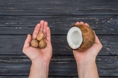 Грецкие орехи и кокос в женских руках Стоковые Фото