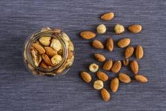 Грецкие орехи, миндалины и фундуки в стеклянной красивой вазе и на серой предпосылке ткани для здоровой закуски Стоковое Фото