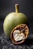 Грецкие орехи на грецком орехе деревянного surfaceA свежем зеленом в корке свежи от дерева Грецкий орех на черной предпосылке Мак Стоковое фото RF