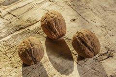 Грецкие орехи на деревенском старом деревянном столе 3 грецкого ореха на деревянном столе Взгляд со стороны Стоковое Изображение RF