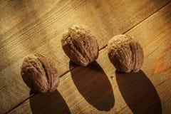 Грецкие орехи на деревенском старом деревянном столе 3 грецкого ореха на деревянном столе Взгляд со стороны Стоковые Изображения RF
