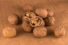 Грецкие орехи раскрыли в коричневой предпосылке стоковые изображения
