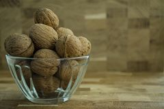 Грецкий орех в стеклянном шаре на деревянной предпосылке r стоковая фотография