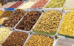 Грецкий орех, даты, фундуки, миндалины, анакардии, изюминки, арахисы и другие хлопья для продажи на рынке стоковые фото