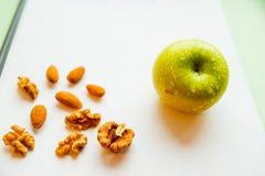 Грецкий орех и зеленое яблоко на белой деревянной предпосылке Гайки, витамины, здоровая концепция еды Обед в офисе Вытрезвитель Стоковая Фотография