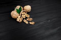 Грецкий орех и стержени грецкого ореха и все грецкие орехи на деревенской черной деревянной предпосылке Стоковая Фотография RF