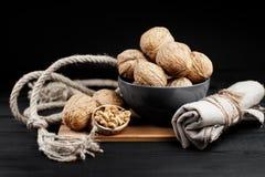 Грецкий орех и стержени грецкого ореха на плите на деревенской деревянной черной предпосылке Стоковая Фотография