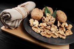 Грецкий орех и стержени грецкого ореха на плите на деревенской деревянной черной предпосылке Стоковая Фотография RF