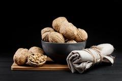 Грецкий орех и стержени грецкого ореха на плите на деревенской деревянной черной предпосылке Стоковые Фото