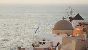 Греческий национальный флаг развевая в ветре на крыше дома в Santorini помыл морским путем сток-видео