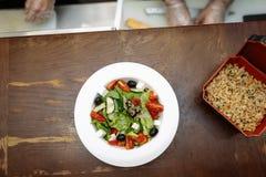 Греческий салат с оливками, томатами, сыром и зелеными цветами в белых плите и рисе в коробке против деревянного стола стоковое фото rf