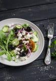 Греческий салат - салат с томатами, огурцами, оливками и сыром фета на белой плите Стоковое фото RF