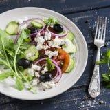 Греческий салат - салат с томатами, огурцами, оливками и сыром фета на белой плите Стоковое Изображение RF