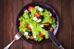 Греческий салат & x28; салат, томаты, сыр фета, огурцы, черное olives& x29; на темной деревянной предпосылке Стоковое Фото