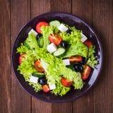 Греческий салат & x28; салат, томаты, сыр фета, огурцы, черное olives& x29; на темной деревянной предпосылке Стоковая Фотография