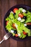 Греческий салат & x28; салат, томаты, сыр фета, огурцы, черное olives& x29; на темном деревянном взгляд сверху предпосылки Стоковое Изображение