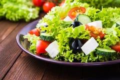 Греческий салат & x28; салат, томаты, сыр фета, огурцы, черное olives& x29; на темном деревянном конце предпосылки вверх Стоковое фото RF