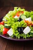 Греческий салат & x28; салат, томаты, сыр фета, огурцы, черное olives& x29; на темном деревянном конце предпосылки вверх Стоковые Изображения RF