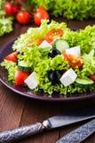 Греческий салат & x28; салат, томаты, сыр фета, огурцы, черное olives& x29; на темном деревянном конце предпосылки вверх Стоковое Фото