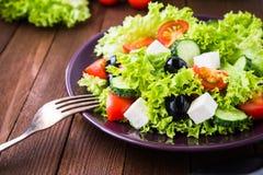 Греческий салат & x28; салат, томаты, сыр фета, огурцы, черное olives& x29; на темном деревянном конце предпосылки вверх Стоковое Изображение