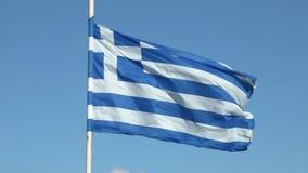 Греческий флаг на поляке развевая над голубой предпосылкой сток-видео