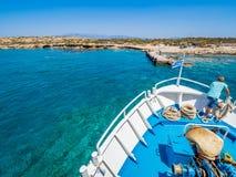 Греческий флаг развевая на смычке плавания шлюпки к острову Chrissi или Вест-Инди в Греции стоковая фотография