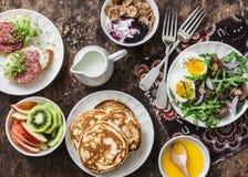 Греческий югурт с всеми хлопьями зерна и ягода sauce, блинчики, arugula, томаты вишни, вареные яйца салат, киви, яблоки приносить Стоковые Фотографии RF