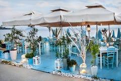 Греческое taverna морем с голубые традиционные деревянные стулья и лампы на вечере, 26 Septembar 2016 Стоковое Фото