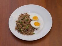 Гречиха и 2 вареного яйца на белой плите Деревянное backgroun Стоковые Изображения RF