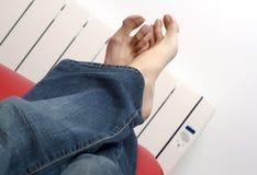 Грея ноги против радиатора Стоковые Изображения RF