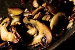 Грибы жаря в масле в сковороде, конце-вверх Стоковые Фото