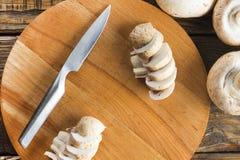 Грибы Champignon и нож на деревянной разделочной доске Взгляд сверху стоковое изображение rf