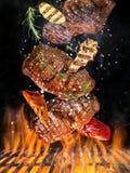 Гриль чайника при горячие брикеты, решетка литого железа и вкусные стейки говядины летая в воздух стоковая фотография