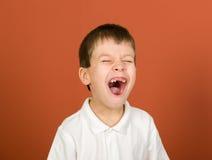 Гримасничая портрет мальчика на коричневом цвете Стоковые Фото