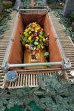 Гроб с bouqet цветков в могиле Стоковое Изображение