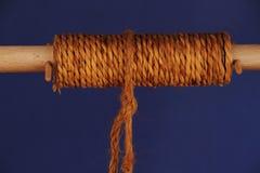 Грубая веревочка вокруг деревянного шпинделя - голубая предпосылка Стоковые Изображения