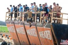 Грубое Mudder: Гонщики скача прогулка планка Стоковое Фото