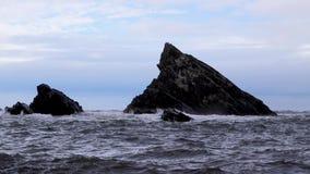Грубые бурные волны разбивая против стога утеса моря в Шотландии во время после полудня осени бурного сток-видео