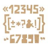 Грубые номера и символы отрезали из бумаги на предпосылке картона Стоковое Фото