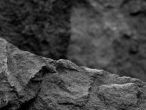 Грубый текстурированный утес с фокусом переднего плана с предпосылкой запачканной камнем черно-белой Стоковое Изображение RF