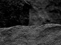 Грубый текстурированный утес с фокусом переднего плана с предпосылкой запачканной камнем черно-белой Стоковое фото RF