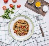 Грузинское блюдо овечки с баклажаном и овощами на белой плите с травами и томатами и петрушкой с вилкой на checkered Стоковое Изображение