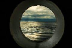 Грузите взгляд окна или иллюминатора с расслабляющим seascape и темными серыми облаками Стоковая Фотография RF