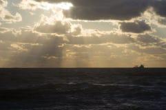 Грузите на горизонте в море на заходе солнца Стоковое Изображение RF