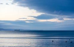 Грузите на штиле на море в свете сини желтого цвета восхода солнца Стоковое Изображение RF