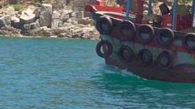 Грузите плавать с автошинами автомобиля на борту в голубом море на ландшафте горы скалы Плавание шлюпки в морской воде бирюзы акции видеоматериалы