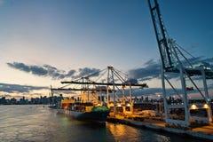 Грузовой корабль и краны в морском порте на небе вечера Морской порт или стержень контейнера Перевозка и товар доставки стоковые изображения rf