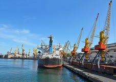 Грузовой корабль и поезд насыпного груза под краном порта Стоковое Изображение
